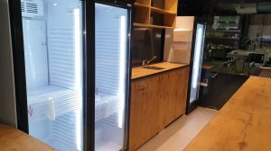 Innen befinden sich drei Glastürenkühlschränke.